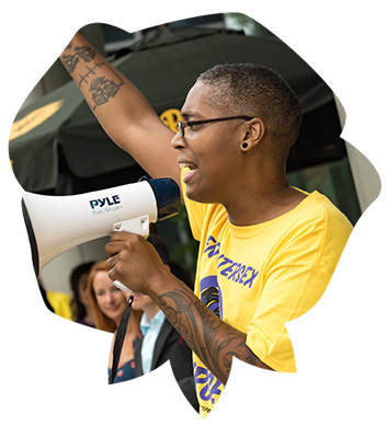 Sean Saifa Wall, IJP co-founder and a Black intersex man, holding a microphone and shouting a chant at an IJP protest.